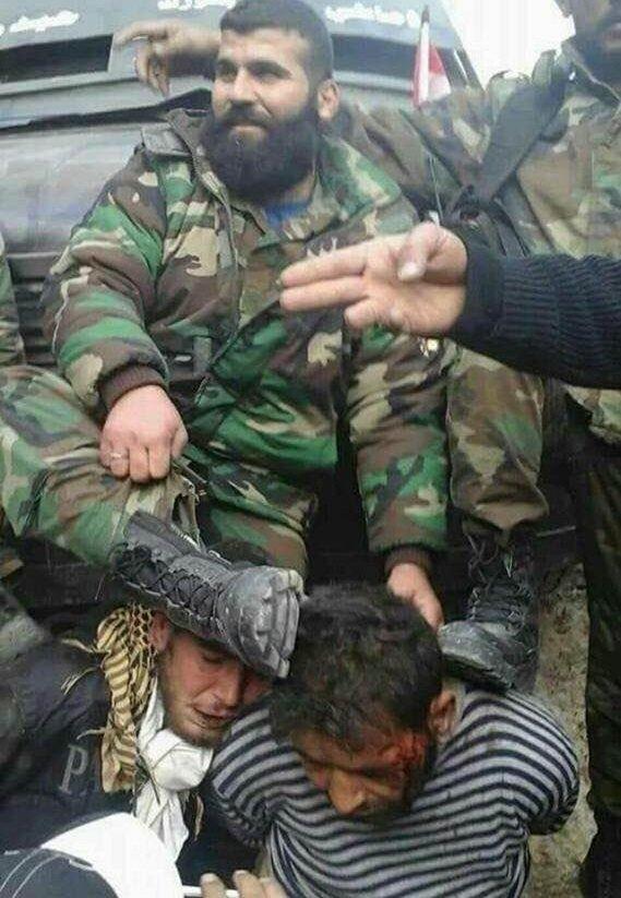Esed askerleri, yakaladıkları iki Türkmen'e korkunç işkenceler yaptı. Askerlerin, ellerini arkadan kelepçeledikleri Türkmenlerin kafalarına bastıkları görülüyor.