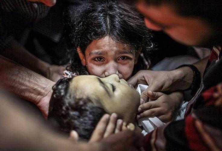 2014 yılında İsrail'in başlattığı 'Koruyucu Hat operasyonunda hayatını kaybeden kardeşine ağlayan küçük bir Filistinli kız.