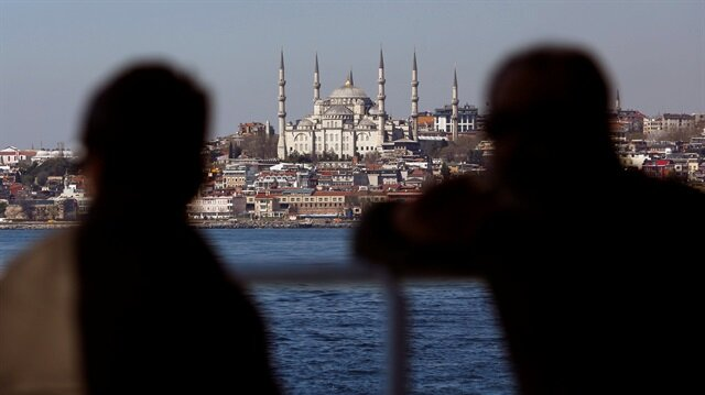 People travel in a ferry with the Ottoman-era Sultanahmet mosque
