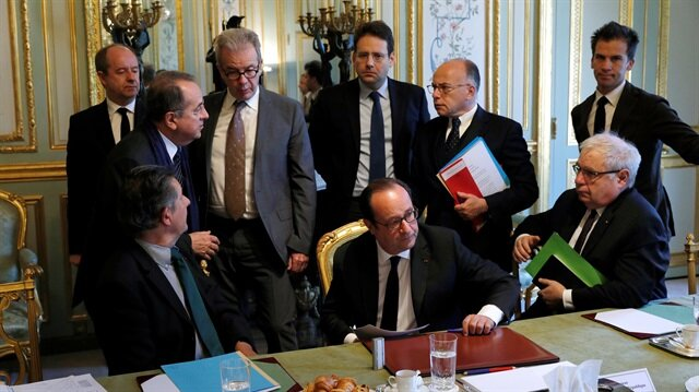 French President Francois Hollande speaks with ministers and officials at the end of a defense council at the Elysee Palace in Paris.