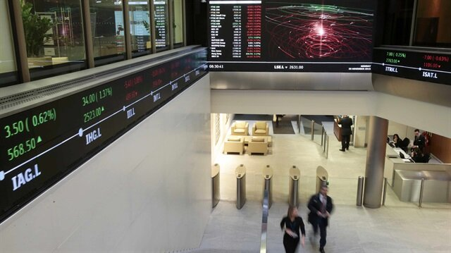 People walk through the lobby of the London Stock Exchange in London, Britain November 30, 2015.