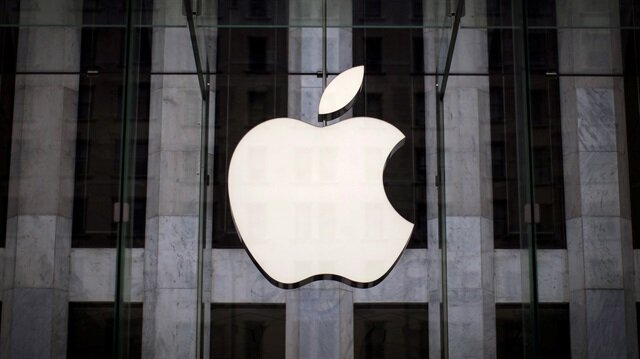 An Apple logo hangs above the entrance to an Apple store