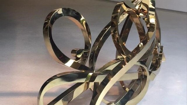 eL Seed's work Paris, Je T'aime rendered as a gold-plated sculpture at the gallery of Le Royal Monceau hotel