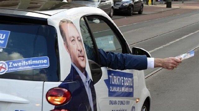 Erdoğan'ın konuşmalarını arabadan seslendirerek, yoldan geçen Türklere, 24 Eylül'ü unutmayın deyip seçim afişlerini dağıttılar.
