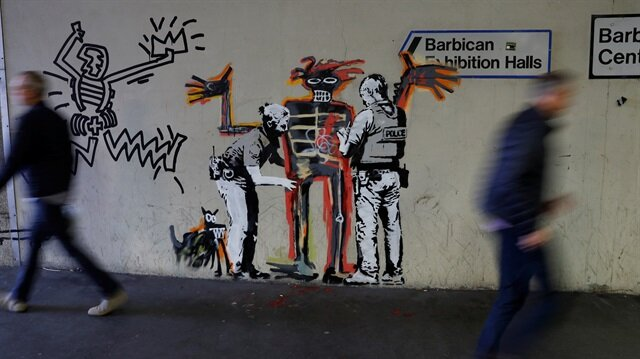 People walk past a mural painted by the artist Banksy near the Barbican Centre in London, Britain.
