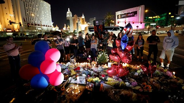 People gather at a makeshift memorial in the middle of Las Vegas Boulevard