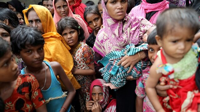 Rohingya refugees wait for humanitarian aid to be distributed