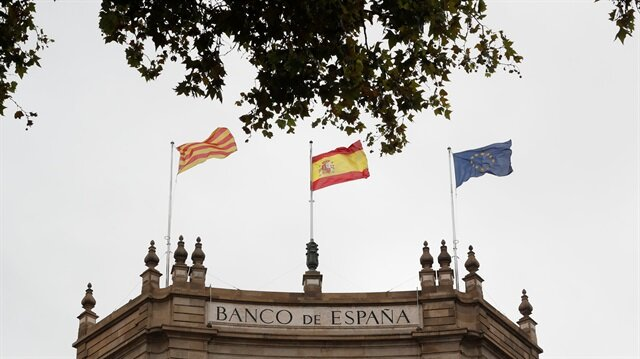 A Catalonian, Spanish and European flag fly on the roof of the Bank of Spain