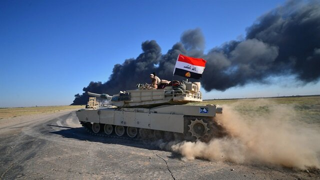 Iraqi army members ride on a tank on the outskirts of Hawija, Iraq.