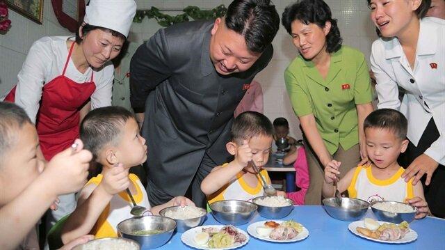 Kuzey Kore lideri Kim Jong-un çocuklarla konuşuyor.