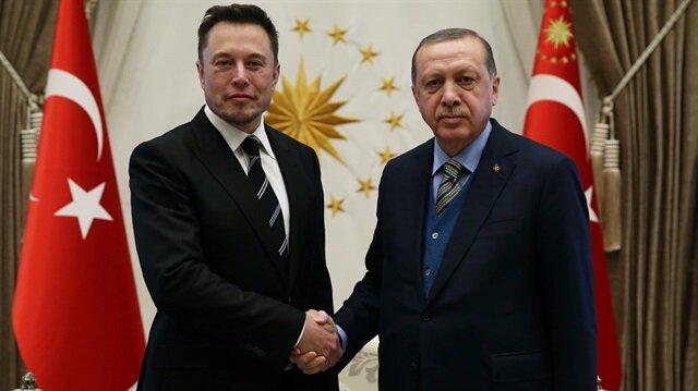 Cumhurbaşkanı Erdoğan ve Elon Musk, üzerinde Türksat yazan SpaceX Falcon 9 roketlerine bakıyor.