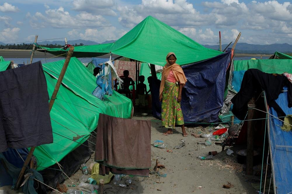 A Rohingya Muslim woman stands as she waits to cross the border to go to Bangladesh, in a temporary camp outside Maungdaw, northern Rakhine state, Myanmar.