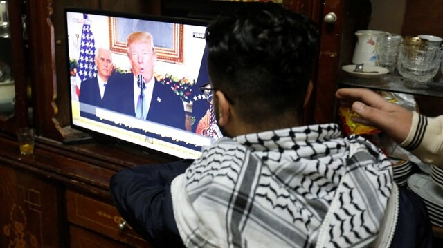 A Palestinian refugee watches a televised broadcast of U.S. President Donald Trump
