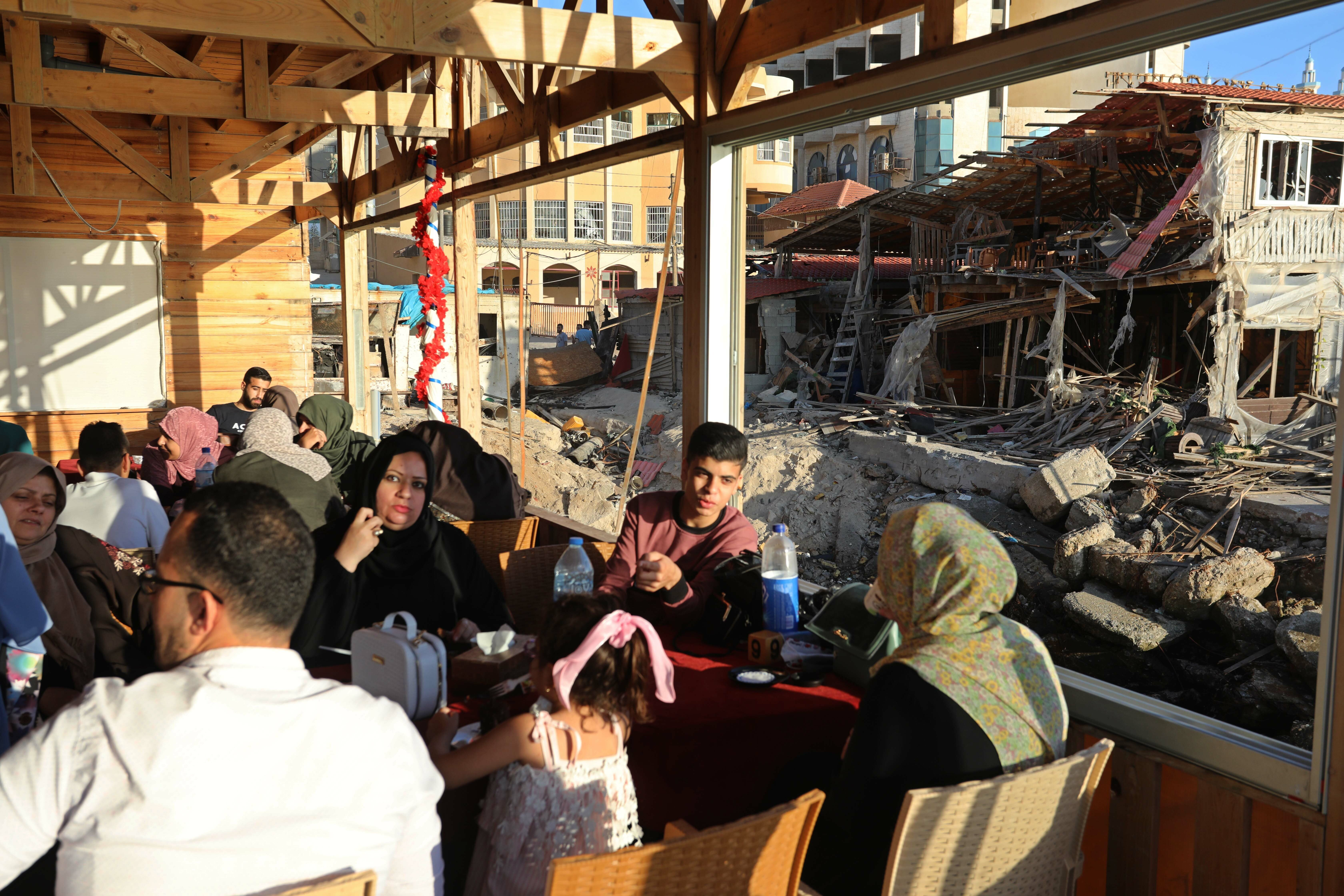 Palestinians converge at destroyed cafe following Israeli attacks on Gaza
