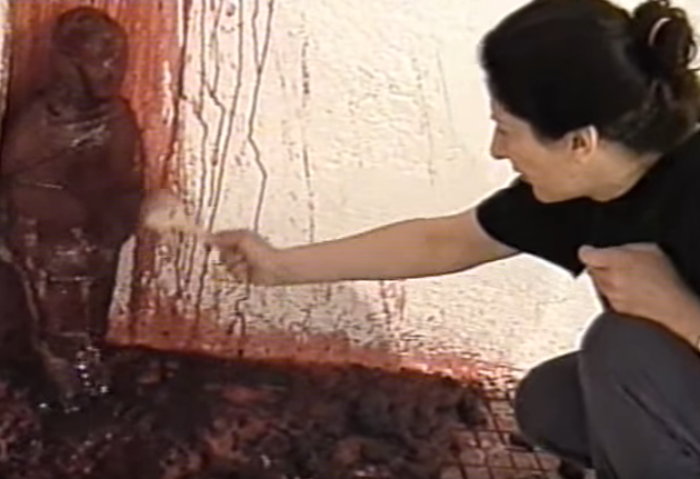 A screenshot from Marina's 'Spirit Cooking' video where she throws pig blood at a statue shaped like a small child.