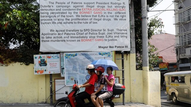 A motorist drives a motorcycle past a banner denouncing the Bonnet Gang, a group allegedly nvolved in drug related killings