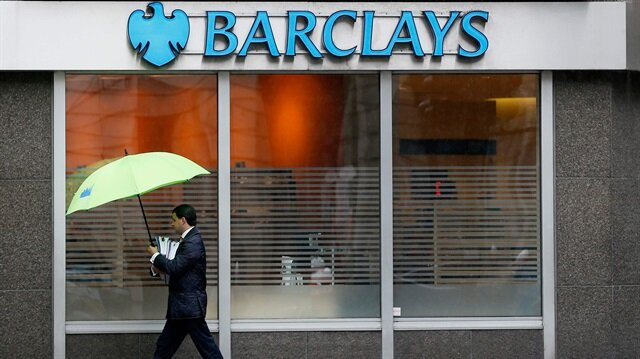 man shelters under umbrellas as he walks past a Barclays branch in central London