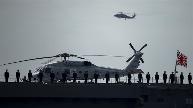 Military personnel stand on deck of the Izumo helicopter carrier of the Japanese Maritime Self-Defense Force (JMSDF) during its fleet review at Sagami Bay, off Yokosuka, south of Tokyo
