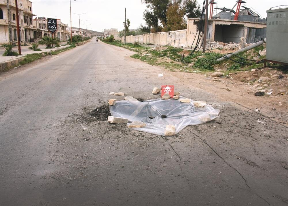 : A poison hazard danger sign is seen in the town of Khan Shaykun, Idlib province, Syria.