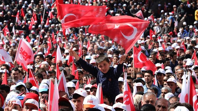 """Turkish citizens hold up Turkish flags and banners reading """"Yes."""""""
