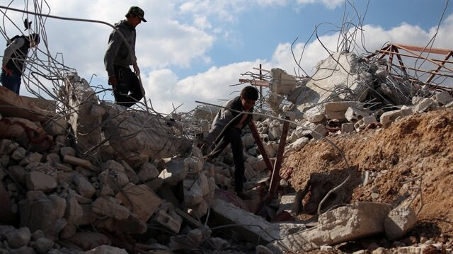 Youth inspect rubble of a damaged house after an airstrike