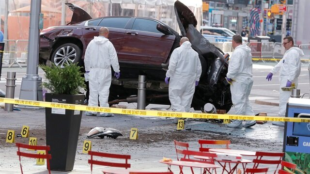 Emergency personnel inspect a vehicle involved in striking a number of pedestrians in Times Square in New York.