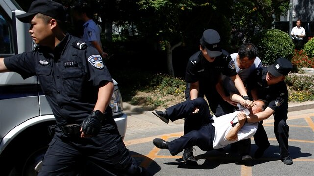 Police detain a man as people protest against a local authoritiy's decision to reassign their children to an undesired school in Beijing, China June 14, 2017.