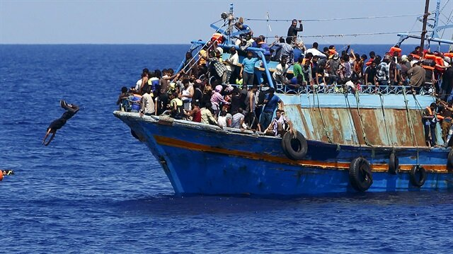 A migrant dives into the water from an overloaded wooden boat during a rescue operation