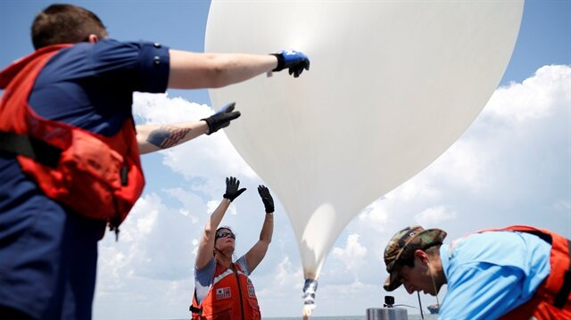 College of Charleston professor Dr. Cassandra Runyon (Center) releases a balloon during a test