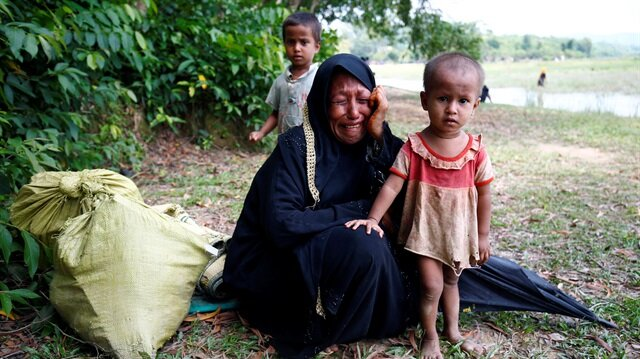 A Rohingya woman cries with her child, after being restricted by the members of Border Guards Bangladesh (BGB) to further enter the Bangladesh side, in Cox's Bazar, Bangladesh August 28, 2017.