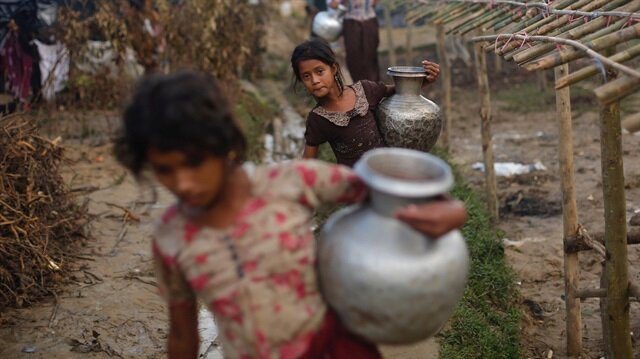 Rohingya refugee girls carry metal pitchers with water at Balukhali makeshift refugee camp in Cox's Bazar, Bangladesh.