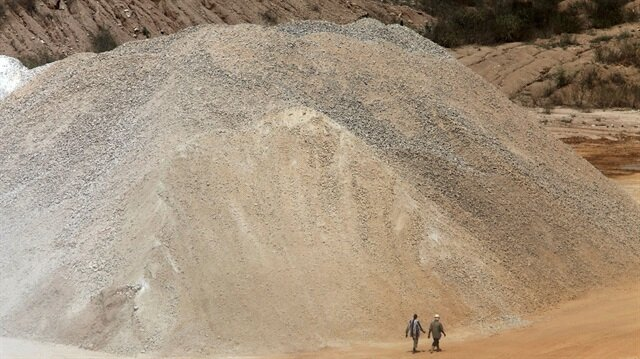 Workers walk past a pile of limestone at the Dangote Cement mine in Obajana village in Nigeria's central state of Kogi November 8, 2010.