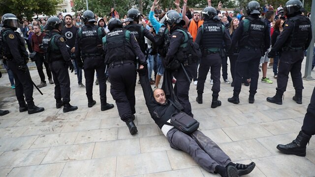 A man is dragged away by Spanish Civil Guard officers, outside a polling station, for the banned independence referendum, where Catalan President Carles Puigdemont was supposed to vote in Sant Julia de Ramis, Spain October 1, 2017.