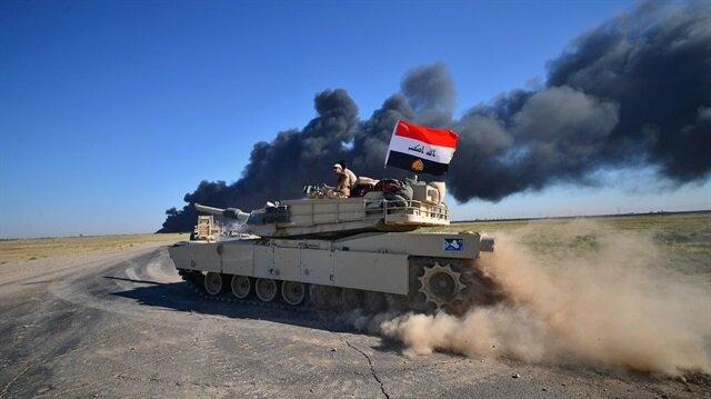 Iraqi army members ride on a tank on the outskirts of Hawija, Iraq.