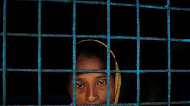 A Rohingya refugee who crossed the border from Myanmar this week stands at a window