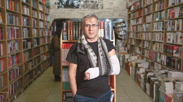 """Kitabevi camlarını silip para yerine kitap alan Metin Ulusoy, """"Kitabı seviyorum. Hayat boyu hem cam sildim hem de kitaplarımı okudum"""" diyor."""