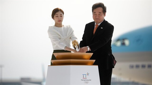 Honorary Ambassador Yuna Kim and Prime Minister Lee Nak-yon light the cauldron with the Olympic flame at the Incheon International airport in Incheon