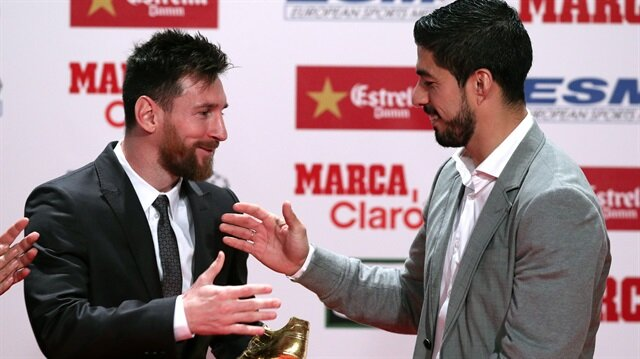 Barcelona's Lionel Messi is congratulated as he receives his fourth Golden Boot trophy from Luis Suarez during a ceremony in Barcelona