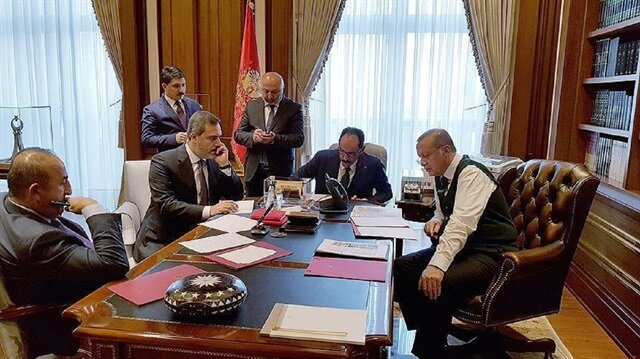 Turkish President Recep Tayyip Erdogan (R) appears while talking to US President Donald Trump over the phone while Presidential spokesman Ibrahim Kalin (CR), Chief of Turkish Intelligence Agency Hakan Fidan (CL) and Foreign Minister Mevlut Cavusoglu (L) join him.