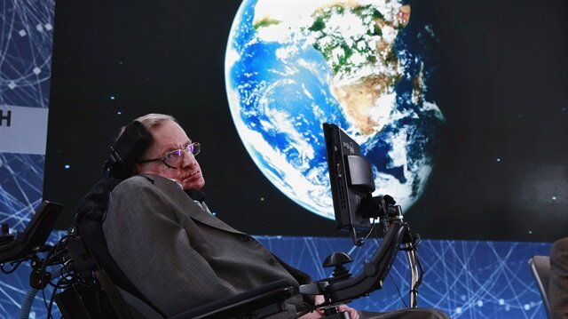 Physicist Stephen Hawking sits on stage