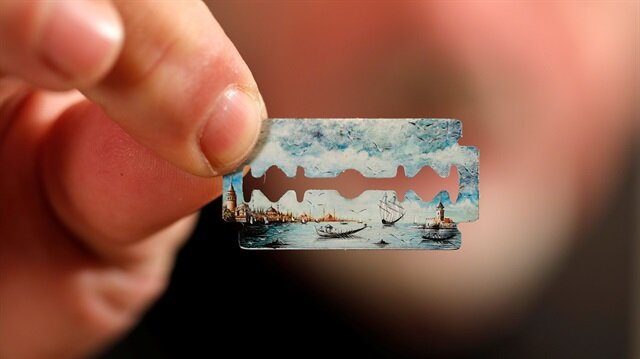 Turkish micro artist Hasan Kale displays one of his art work on a razor blade at his office