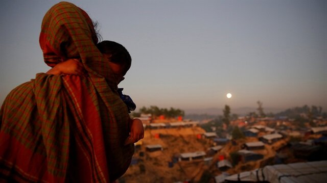 A Rohingya refugee looks at the full moon with a child in tow at Balukhali refugee camp near Cox's Bazar, Bangladesh