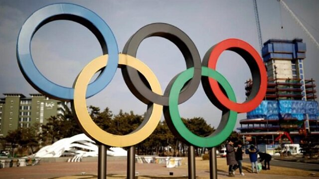 People walk past the Olympic rings in Gangneung, South Korea