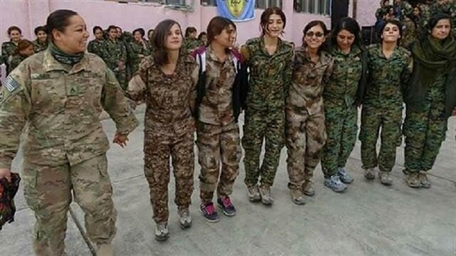 Photo showing an American soldier taking part in a folk dance with YPG terrorists