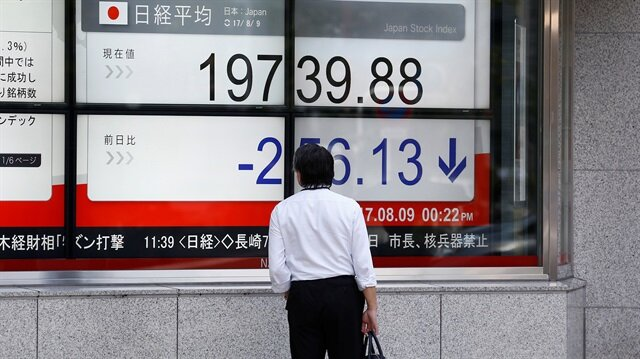 A man looks at an electronic board showing Japan's Nikkei average outside a brokerage