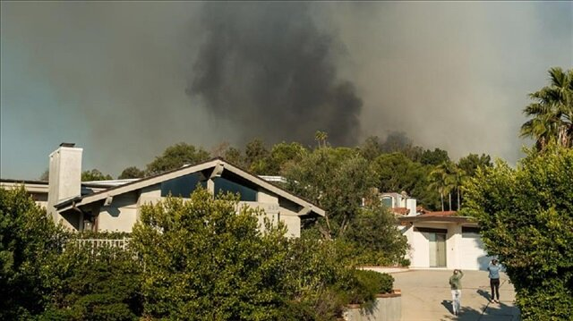 Home owners watch as the Skirball Fire burns Wednesday, December 6, 2017 in Bel Air, California, United States. Interstate 405 was shutdown North of Westwood as the fire neared the road.