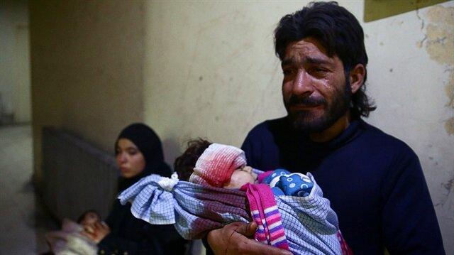 Şam'ın Doğu bölgesinde hava saldırısında katledilen 2 yaşındaki oğlunun minik bedenini tutan baba Mahmoud al-Bash... (Fotoğraf: Reuters)