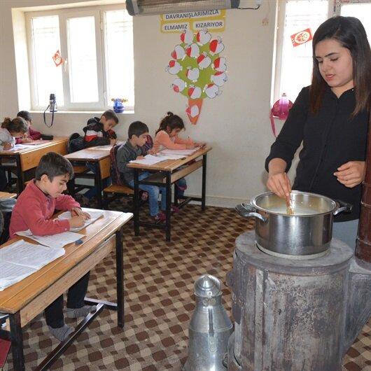 Öğrencilerine odun sobasında puding hazırlıyor