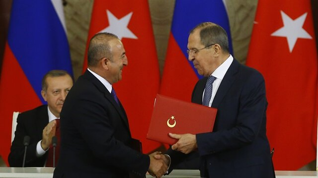 Turkish Foreign Minister Mevlüt Çavuşoğlu (2nd L) and his Russian counterpart Sergei Lavrov (R) shake hands.