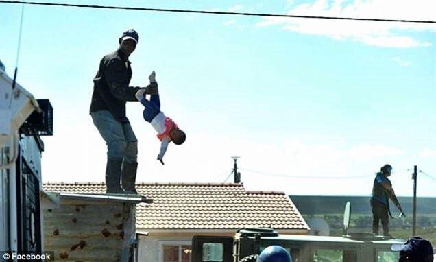Protestoyu izleyen bir grup vatandaş, protestocunun çocuğu aşağı atması için tezahürat yaptı.
